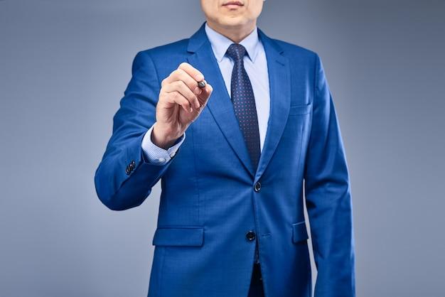 Un uomo d'affari in un abito blu detiene una penna