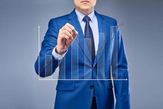 Un uomo d'affari in un abito blu disegna un grafico