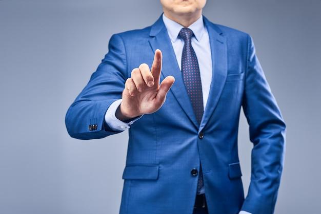Un uomo d'affari in un abito blu gli mette un dito davanti