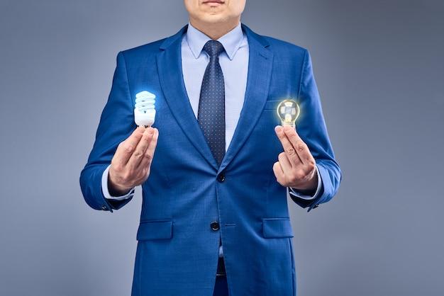 Un uomo d'affari in un abito blu in possesso di due lampadine accese