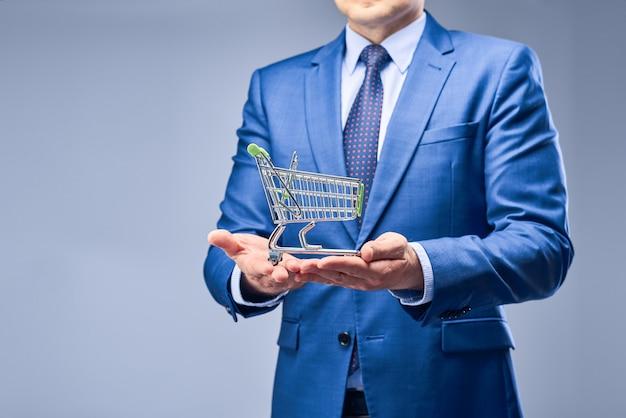 Un uomo d'affari in un abito blu in possesso di un carrello