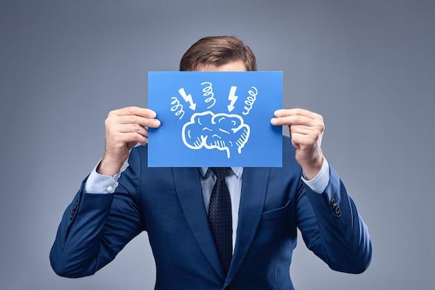 Un uomo d'affari in un abito blu in possesso di un foglio di carta blu