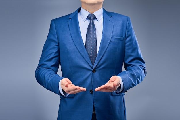 Un uomo d'affari in un abito blu tiene le mani davanti a lui