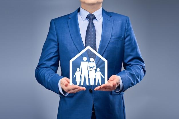 Un uomo d'affari in un abito blu tiene una casa con la sua famiglia di fronte a lui