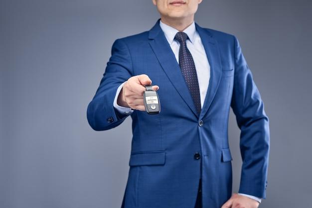 Un uomo d'affari in un vestito blu che tiene le sue chiavi della macchina