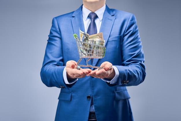 Un uomo d'affari in un vestito blu che tiene soldi