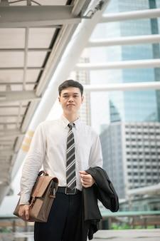 Un uomo d'affari in una camicia bianca con cravatta e abito nero sta andando a lavorare