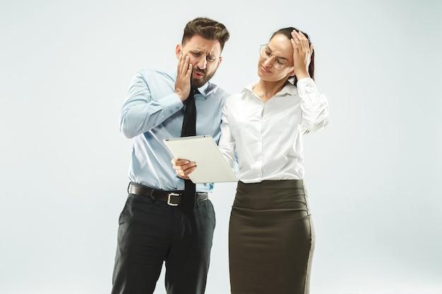Un uomo d'affari mostra il portatile al suo collega in ufficio.