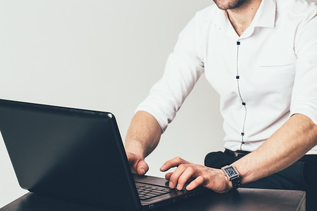 Un uomo d'affari si siede al tavolo e lavora dietro un computer portatile in ufficio. un uomo sta scrivendo su un computer portatile un messaggio