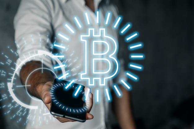 Un uomo d'affari tiene in mano un telefono, un'icona bitcoin, affari, nuove tecnologie.