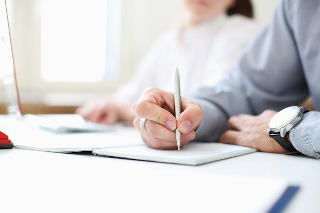 Un uomo d'affari tiene in mano una penna. metti una firma. immagine con profondità di campo.