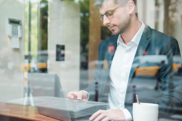 Un uomo d'affari visto attraverso il vetro con carta di credito per lo shopping online nella caffetteria