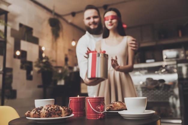 Un uomo dà un regalo ad una ragazza con gli occhi chiusi