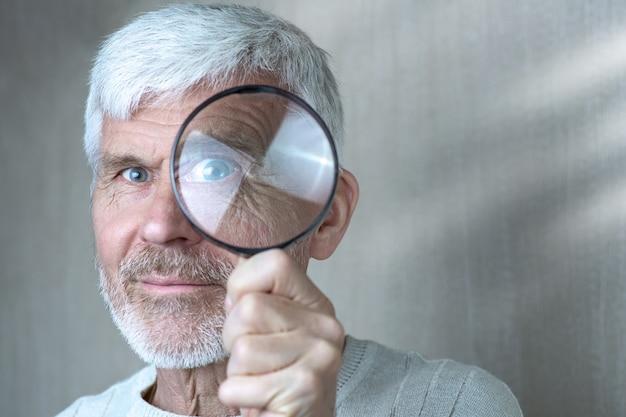 Un uomo dai capelli grigi in abiti leggeri guardando attraverso una lente di ingrandimento