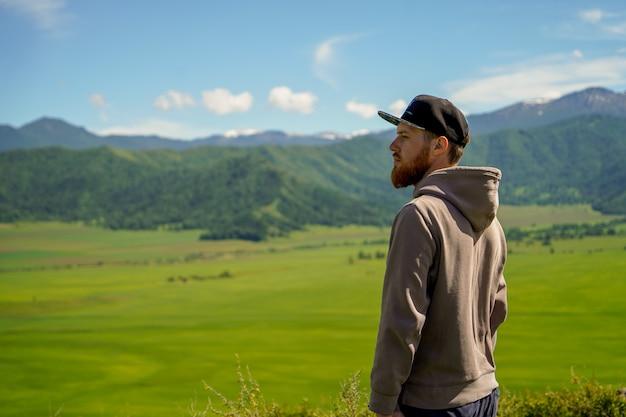 Un uomo dalla barba rossa in felpa con cappuccio davanti al campo verde e alle montagne