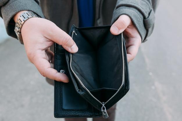 Un uomo della mano del primo piano apre un portafoglio vuoto