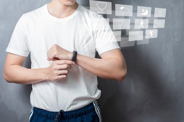 Un uomo dello sport sta usando la banda intelligente con il dispositivo dello schermo virtuale