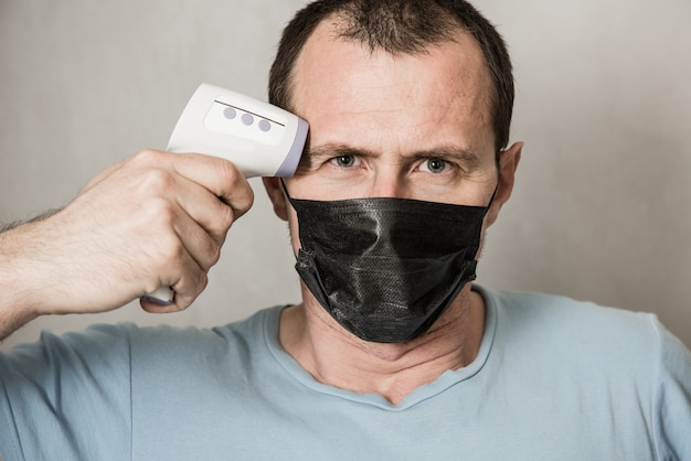 Un uomo depresso che indossa la maschera protettiva pronto per l'uso del termometro a infrarossi sulla fronte per controllare la temperatura corporea per i sintomi del virus - concetto di epidemia di virus epidemico. coronavirus.termometro pistola