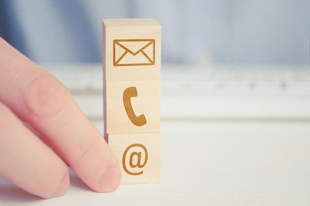 Un uomo detiene un cubo di legno con l'immagine di un telefono, e-mail, lettere simbolo. i contatti per la comunicazione, i metodi di lavoro necessari negli affari.