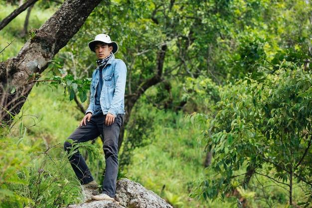 Un uomo di escursionismo felice cammina attraverso la foresta con uno zaino.