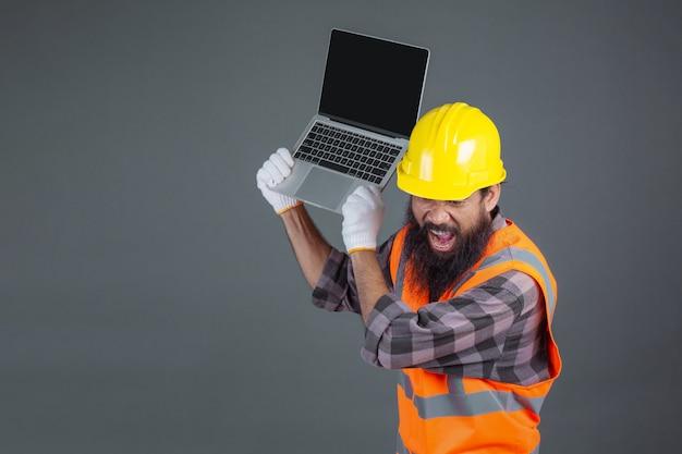 Un uomo di ingegneria che indossa un casco giallo in possesso di un notebook su un grigio.
