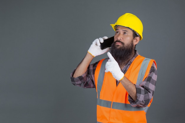 Un uomo di ingegneria che indossa un casco giallo in possesso di un telefono su un grigio.