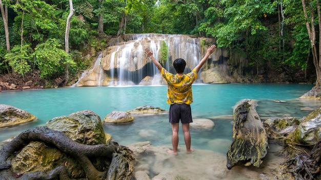 Un uomo di libertà si sta godendo la bellissima cascata nella foresta tropicale