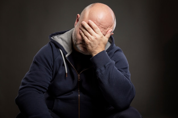 Un uomo di mezza età calvo serio con una maglietta nera è seduto con la mano in faccia. nero .
