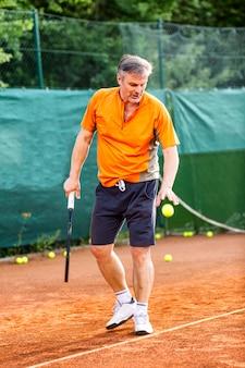 Un uomo di mezza età gioca a tennis su un campo con una superficie di terra naturale in una soleggiata giornata estiva.