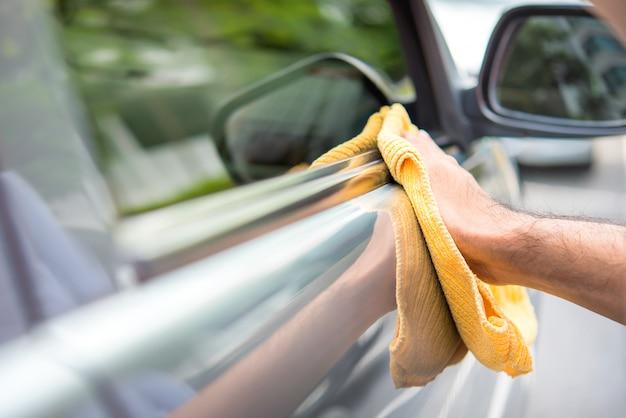 Un uomo di pulizia auto con panno in microfibra giallo