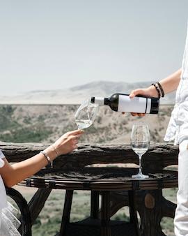 Un uomo di vista frontale che versa il vino nel vetro delle femmine sul vino della gente umana dell'alcool di vista della città