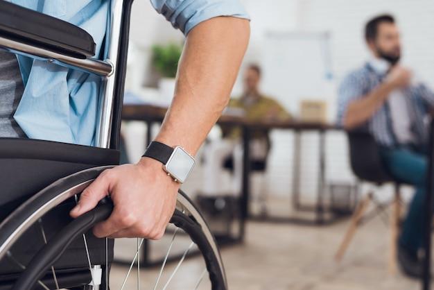 Un uomo disabile è seduto su una sedia a rotelle.