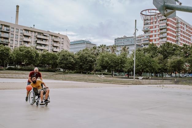 Un uomo disabile in sedia a rotelle gioca a basket con un amico