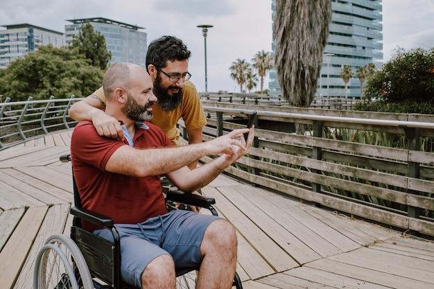Un uomo disabile su sedia a rotelle con il suo assistente in cerca di un telefono cellulare