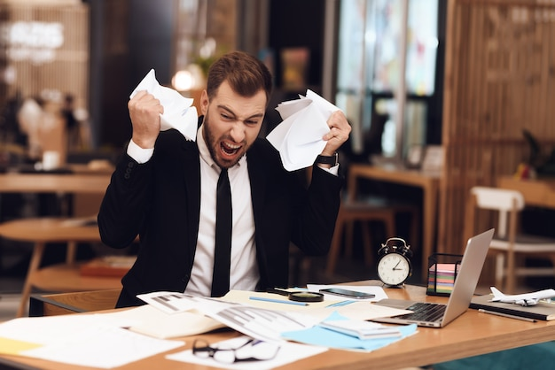 Un uomo è deluso dalla grande quantità di lavoro.