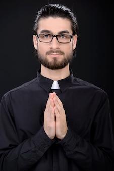 Un uomo è in piedi con gli occhiali e incrociò le braccia.
