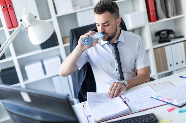 Un uomo è seduto a un tavolo in ufficio, lavora con documenti e beve acqua da una bottiglia.