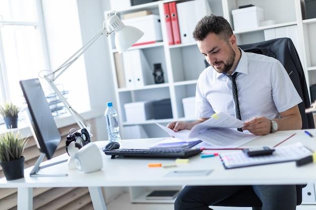 Un uomo è seduto alla scrivania in ufficio e lavora con i documenti.