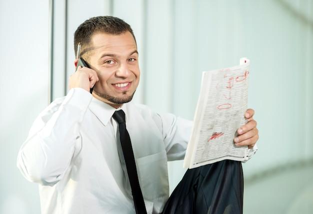 Un uomo è seduto con un giornale e parla al telefono.