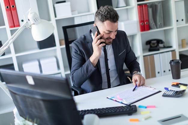 Un uomo è seduto in ufficio al tavolo, parla al telefono e lavora con i documenti.