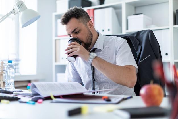 Un uomo è seduto in ufficio, beve caffè e lavora con i documenti.