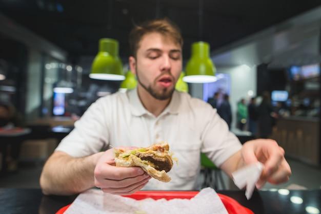 Un uomo è seduto in un ristorante e mangia fast food. l'uomo mangia un hamburger appetitoso. concetto di fast food.