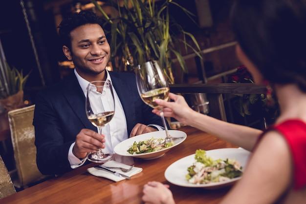 Un uomo e una donna bevono vino ad un appuntamento.