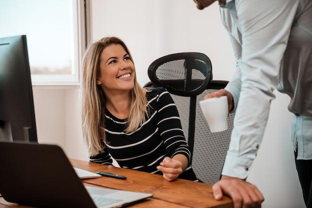 Un uomo e una donna che parlano in una pausa caffè in ufficio.