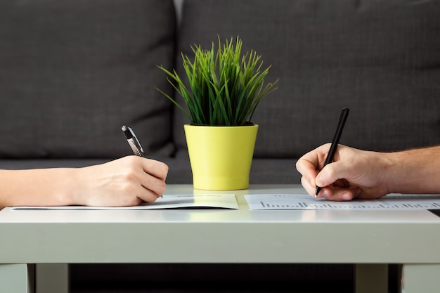 Un uomo e una donna firmano un accordo di divorzio, primo piano. litigio familiare, resa dei conti, divisione della proprietà, accordo di divorzio