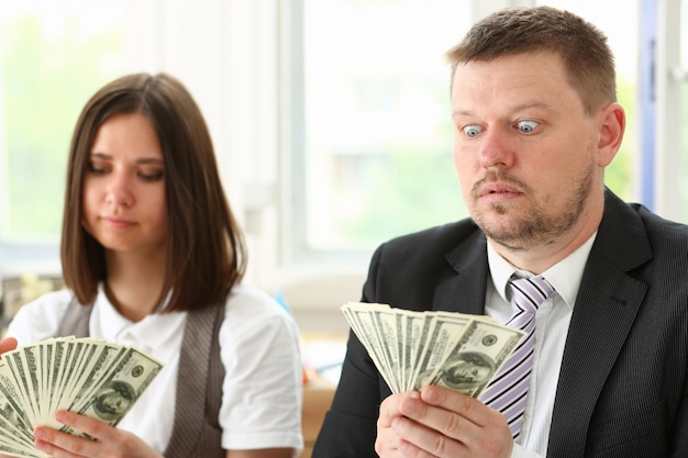 Un uomo e una donna godono di soldi leggeri sotto forma di frode