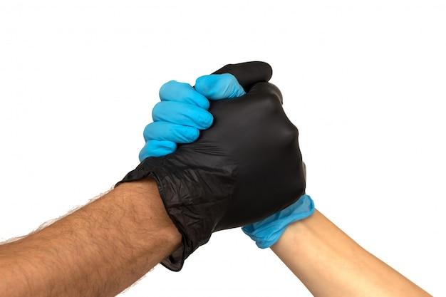 Un uomo e una donna in guanti di gomma multicolori si stringono la mano. isolare su uno sfondo sbiadito. il concetto di un team di successo di stagisti medici