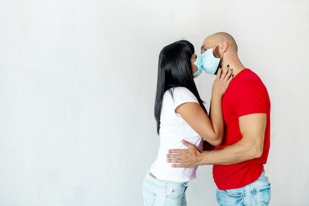 Un uomo e una donna in maschera medica si baciano contro un muro bianco, dimostrando le restrizioni del coronavirus