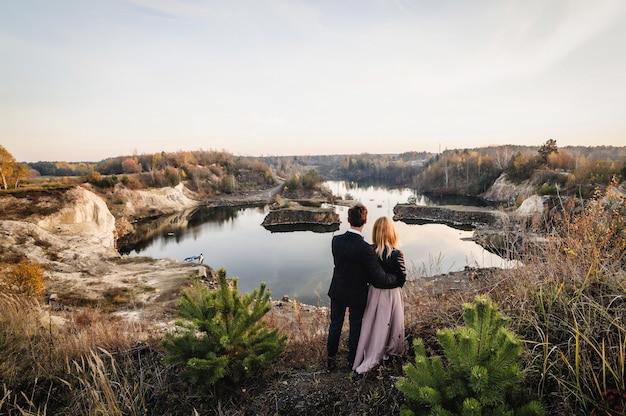 Un uomo e una donna in piedi vicino al lago. guarda in lontananza.