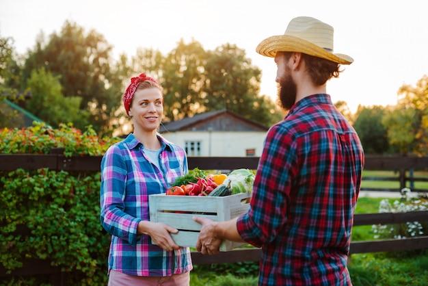 Un uomo e una donna in possesso di una scatola con un raccolto di ortaggi agricoli